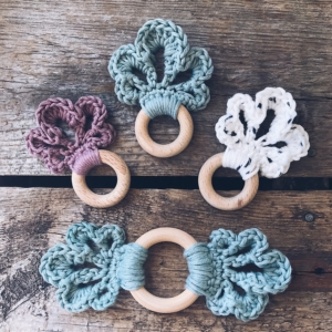 Four LoLo Loop Baby Teethers placed on a wooden backdrop