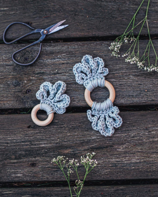 Two different sized teal coloured LoLo Loop Baby teethers are placed on a dark wooden backdrop with two flowers and a scissor framing them
